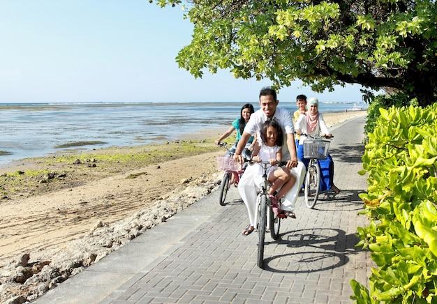 Gelukkige aziatische familie paardrijden fietsen in de mooie ochtend op het strand