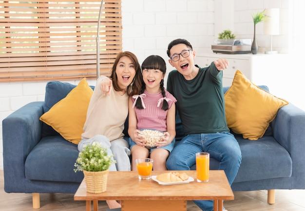 Gelukkige aziatische familie popcorn eten en tv kijken samen op de bank thuis woonkamer. vrije tijd en mensen concept