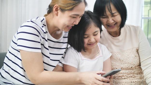Gelukkige aziatische familie speelspelen op smartphone samen, multigeneratie van aziatisch wijfje