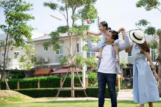 Gelukkige aziatische familie. vader gaf zijn dochter een piggyback in een park in natuurlijk zonlicht en huis. familie vakantie concept