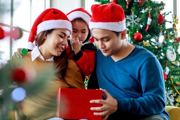 Gelukkige aziatische familie vader moeder en dochter draagt trui met rode en witte kerstman hoed glimlachend lachend met huidige geschenkdoos, bereid je voor om het samen te openen om kerstavond te vieren.