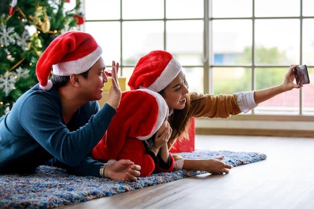 Gelukkige aziatische familie vader moeder en dochter draagt trui met rode en witte kerstman hoed liggend op tapijt vloer moeder met smartphone camera selfie foto vieren kerstavond.