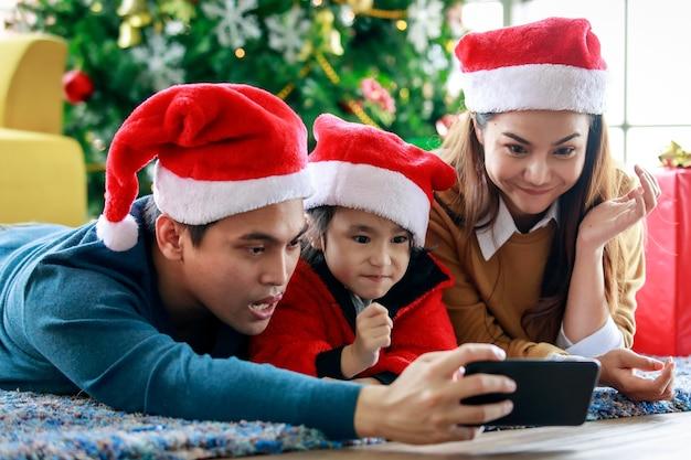 Gelukkige aziatische familie vader moeder en dochter draagt trui met rode en witte kerstman hoed op tapijt vloer met smartphone camera nemen selfie foto samen kerstavond vieren.