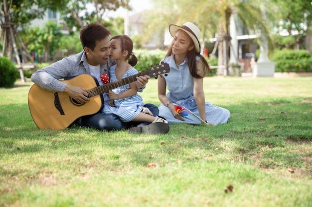 Gelukkige aziatische familie. vader, moeder en dochter in kussen in een park in natuurlijk zonlicht. familie vakantie concept.