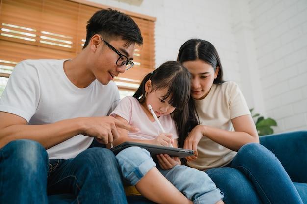 Gelukkige aziatische familie vader, moeder en dochter met behulp van computer tablet technologie zitbank in de woonkamer thuis