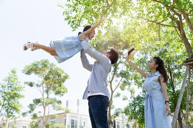 Gelukkige aziatische familie. vader werpt dochter in de lucht in een park bij natuurlijk zonlicht en huis. familie vakantie concept