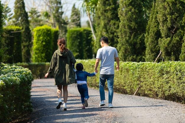 Gelukkige aziatische familie wandelen en hand in hand samen met kinderen in het park. gelukkige familie vader moeder en kind dochter