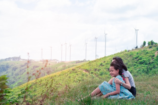 Gelukkige aziatische familiemoeder en dochterzitting bovenop mooie berg met de turbine op achtergrond
