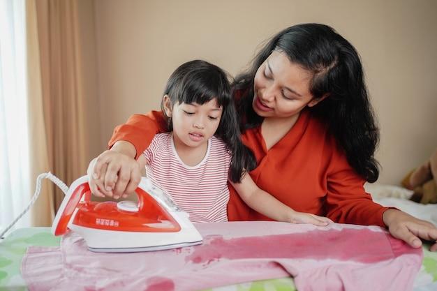 Gelukkige aziatische familiemoeder en weinig babydochter samen bezig met huishoudelijk werk ijzer kleren ijzer thuis.