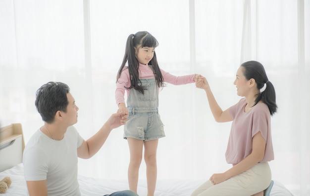 Gelukkige aziatische familiemoeder, vader en dochter op bed in slaapkamer.