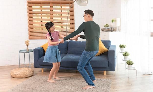 Gelukkige aziatische familievader en kinddochter die thuis dansen.