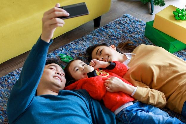 Gelukkige aziatische familievader met smartphonecamera die selfie-foto maakt met moeder en dochter dragen trui op tapijtvloer in de woonkamer om kerstavond en tweede kerstdag thuis te vieren.