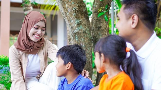 Gelukkige aziatische gezinnen die samen in de tuin spelen en kletsen