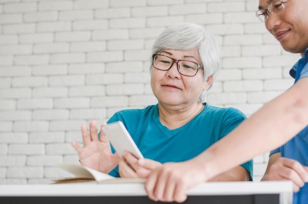 Gelukkige aziatische hogere vrouw die smartphone leren te gebruiken