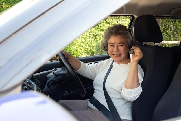 Gelukkige aziatische hogere vrouwenbestuurder die nieuwe autosleutel toont.