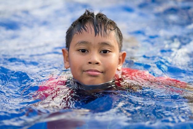 Gelukkige aziatische jong geitjejongen die op zwembad in de zomer zwemmen