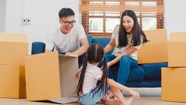 Gelukkige aziatische jonge familiehuiseigenaren in nieuw huis