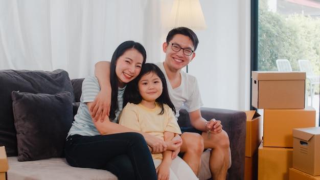 Gelukkige aziatische jonge familiehuiseigenaren kochten nieuw huis. japanse moeder, vader en dochter omhelzen elkaar en kijken uit naar de toekomst in een nieuw huis nadat ze samen in verhuizing op de bank met dozen zijn gaan zitten.