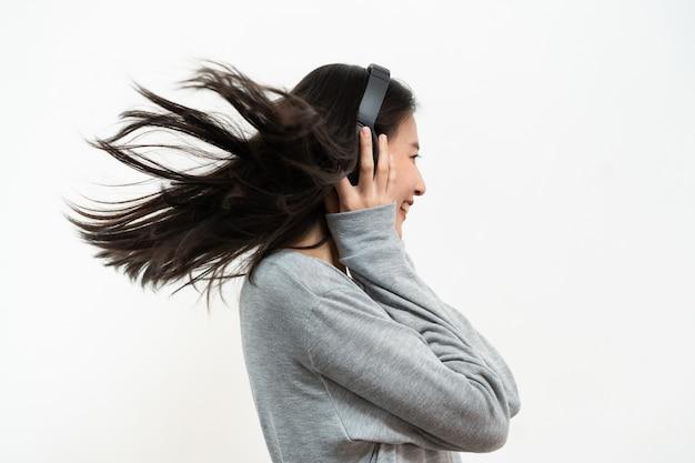 Gelukkige aziatische jonge meisje het luisteren muziek van hoofdtelefoons die op witte achtergrond wordt geïsoleerd.
