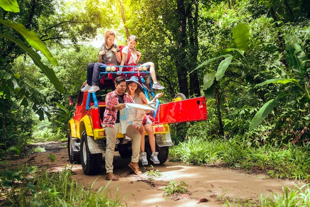 Gelukkige aziatische jonge reizigers met 4wd rijden auto off road in bos, jong stel op zoek naar routebeschrijving op de kaart en nog twee genieten van 4wd rijden auto. jonge gemengd ras aziatische vrouw en man.