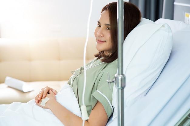 Gelukkige aziatische jonge vrouwenpatiënt die in het ziekenhuisbed en glimlach rusten