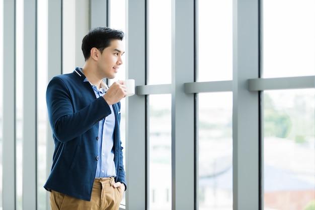 Gelukkige aziatische jonge zakenman die een koffiekop houdt
