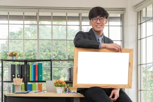 Gelukkige aziatische jonge zakenman die een leeg wit bord houden en op de lijst in bureau zitten.