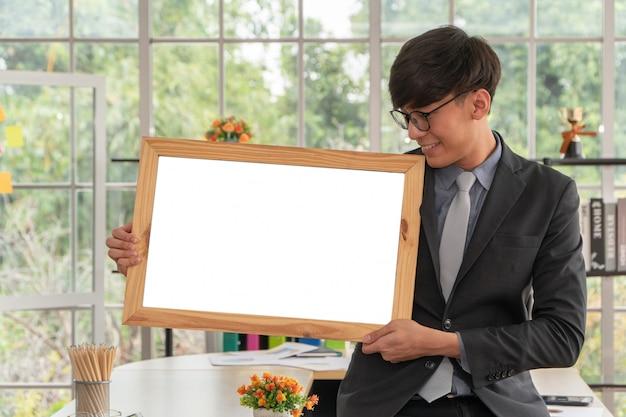 Gelukkige aziatische jonge zakenman die een leeg wit bord houdt en op de lijst in bureau zit.