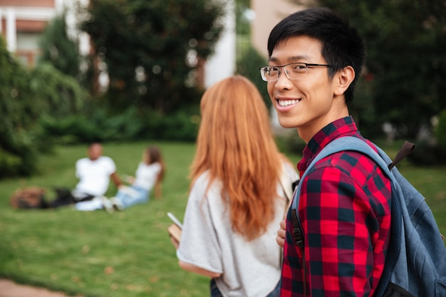 Gelukkige aziatische jongeman student met rugzak die buiten loopt