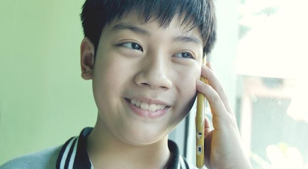 Gelukkige aziatische jongen die met celtelefoon spreekt met glimlachgezicht.
