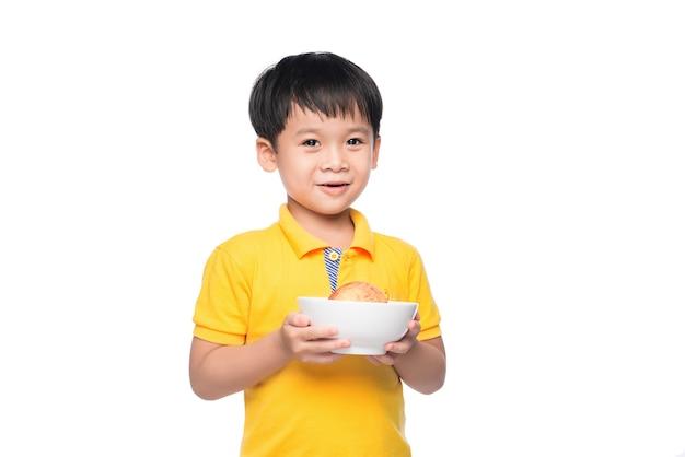 Gelukkige aziatische jongen die rode appel in kom houdt.