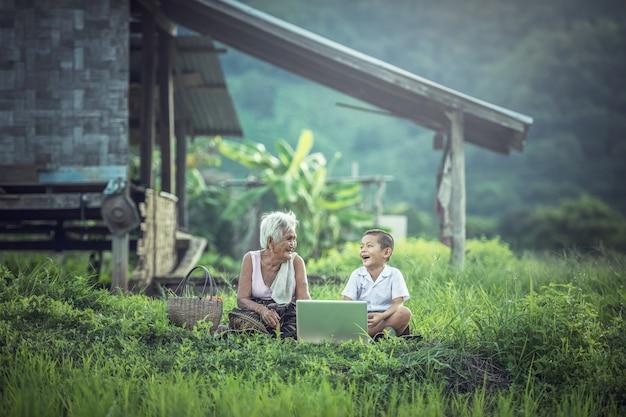 Gelukkige aziatische jongen en grootmoeder die laptop thuis met behulp van, het plattelandsgebied van thailand