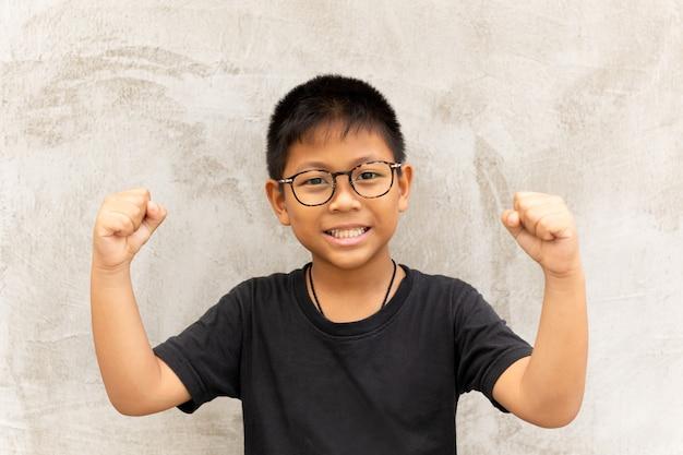 Gelukkige aziatische jongen met glazenhanden omhoog en glimlachend over grijze achtergrond.