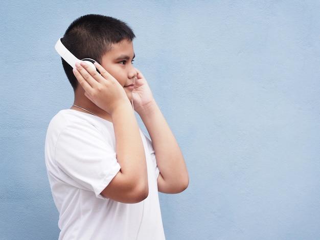 Gelukkige aziatische jongen met wit overhemd die hoofdtelefoon dragen en aan muziek over blauwe muur luisteren