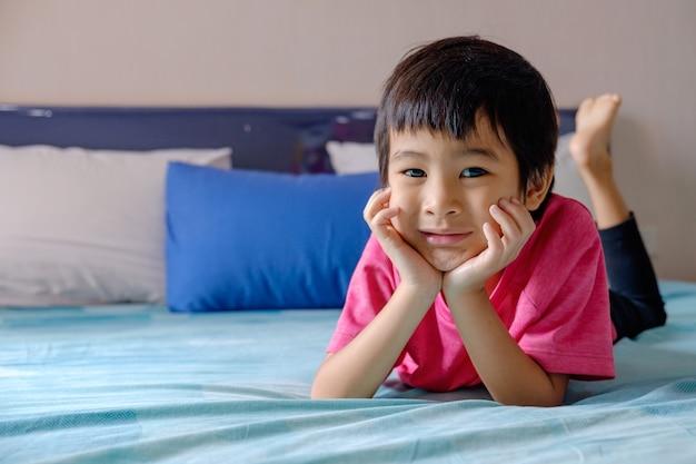 Gelukkige aziatische jongenshand aan wang op blauw bed