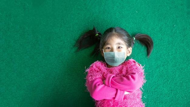 Gelukkige aziatische kinderen dragen masker op groene ondergrond