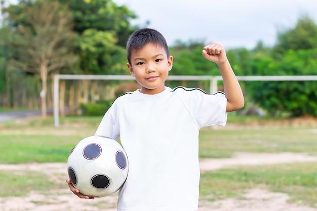 Gelukkige aziatische kindjongen die en een voetbalstuk speelgoed in zijn handen spelen houdt. hij draagt een wit overhemd op de speelplaats. gelukkige en glimlachende jongen. sport en kind concept.