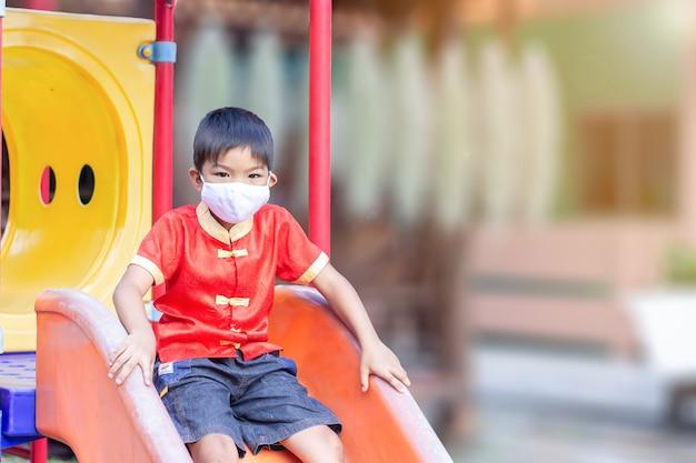 Gelukkige aziatische kindjongen die en stoffenmasker glimlacht draagt, speelt hij met schuifbalkstuk speelgoed bij de speelplaats,