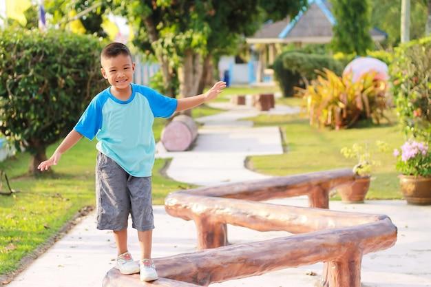 Gelukkige aziatische kindjongen warmt zijn lichaam op voordat hij rent en oefent. hij loopt op een houten bar op de speelplaats.