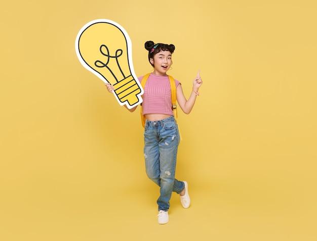 Gelukkige aziatische kindstudent die gloeilamp met schooltas houdt