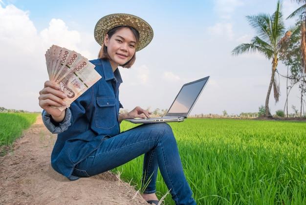 Gelukkige aziatische landbouwersvrouw die en laptop computer met het houden van bankbiljetgeld zitten gebruiken bij groen rijstlandbouwbedrijf