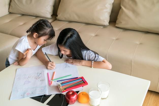 Gelukkige aziatische leuke meisjes die thuis schilderen