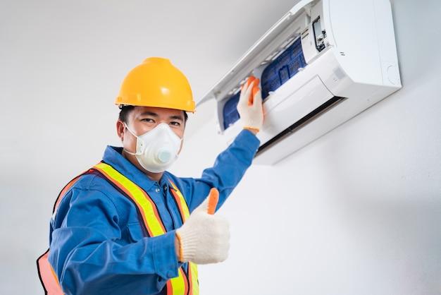 Gelukkige aziatische man draagt een veiligheidsmasker om te voorkomen dat stoftechnicus airconditioner binnenshuis schoonmaakt, airconditionertechnicus