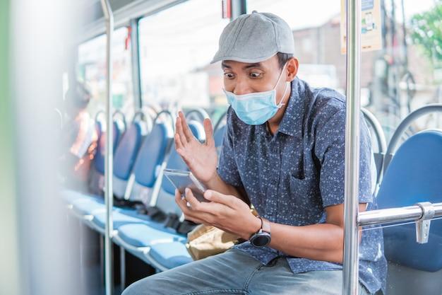 Gelukkige aziatische man juichen vieren kijken naar smartphone terwijl in openbare bus met masker