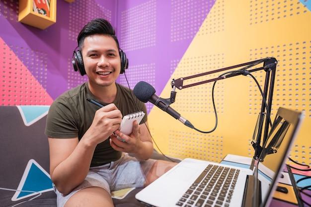 Gelukkige aziatische man neemt een podcast op in zijn studio, let op