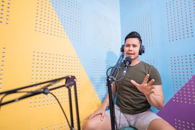 Gelukkige aziatische man neemt een podcast op in zijn studio