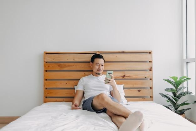 Gelukkige aziatische man voelt zich ontspannen met smartphone op zijn bed his