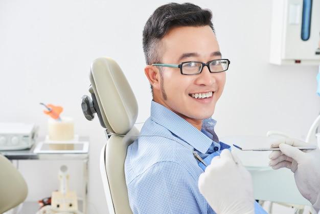 Gelukkige aziatische mens bij tandarts