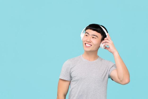 Gelukkige aziatische mens die hoofdtelefoons dragen die aan muziek en het glimlachen luisteren