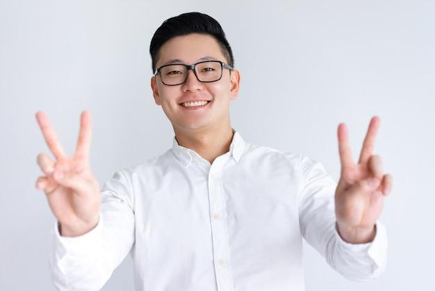 Gelukkige aziatische mens die twee overwinningstekens toont
